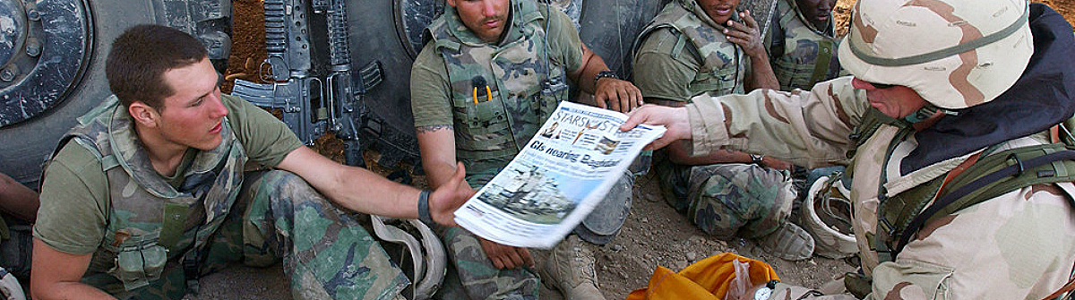 Image of soldier passing out newspaper